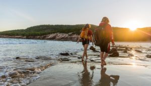 A teenage boy and girl walk on Sand Beach after a hike in Maine's Acadia National Park. ©Jerry and Marcy Monkman/EcoPhotography